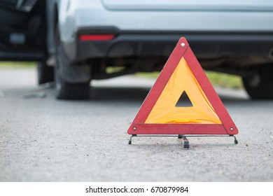 Red emergency stop sign or warning triangle and broken silver car on the road