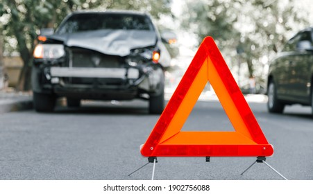 Red emergency stop triangle sign on road in car accident scene. Broken SUV car on road at traffic accident. Car crash traffic accident on city road after collision. Long web banner