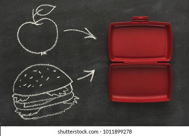 Red empty open plastic lunch box for food storage on black chalk board with copy space and drawn apple and burger, top view