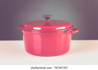 Red enameled cast iron covered dutch oven on a white background.