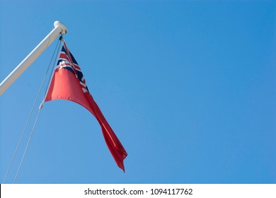 The Red Ensign flutters gently in the breeze set against a clear blue sky.