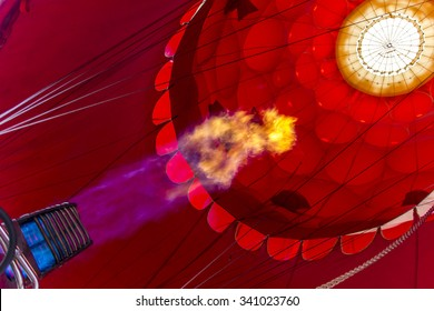 Red envelope of the hot air balloon with a fire from a burner