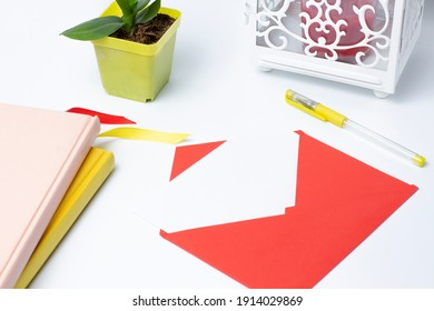 Red envelope on a white desk with a lantern and a small plant, place for your text.