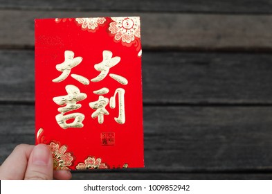 Red envelope packet chinese new year 2018, hongbao with the character 'good luck' in hand wooden background for Chinese New Year
