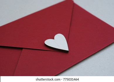 Red Envelope with Wooden Heart Shaped figure. Hand crafted Love Letter for Saint Valentines Day celebration. Celebrate 14 February.