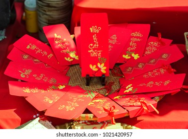 "Red envelopes Lunar New Year Calligraphy decorated with text ""Merit, fortune, longevity"" in Vietnamese means anyone receives money from envelope will be lucky, successful, make a lot of money"