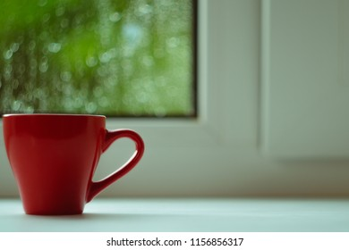 The red espresso cup on white windowsill. On background window and rain. Cup located at left of frame.