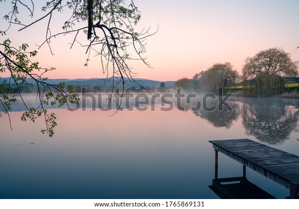 Red evening light on a lake with a wooden jetty