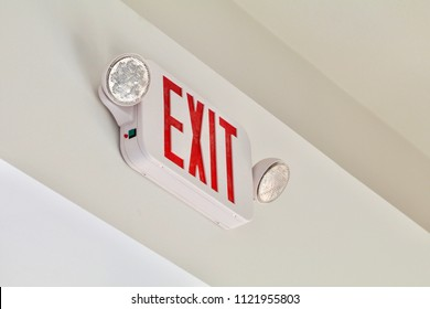 A red exit sign with emergency lights shows above a door.
