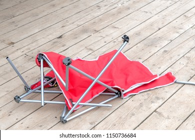 A red fabric broken beach or lawn chair on a wooden deck. The metal legs are broken and in disarray.