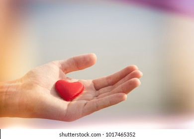 Red fabric heart lay on palm of hand with sea on background. Valentine day. Purple pink blurred