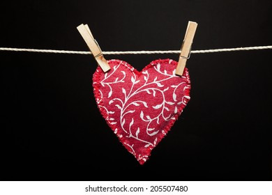 Red fabric Valentine heart hanging on a line with clothes pegs over black background