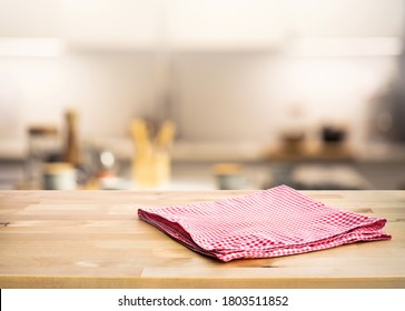 Red fabric,cloth on wood table top on blur kitchen counter (room)background.For montage product display or design key visual layout.