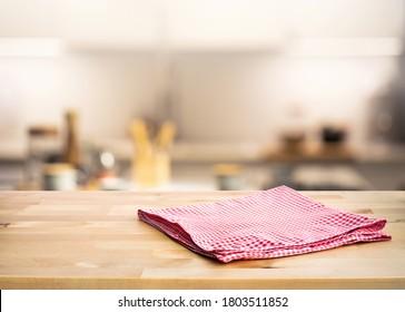 Roter Stoff, Stoff auf Holztisch oben auf unscharfem Küchentisch (Zimmer)Hintergrund.Für die Montage Produkt-Display oder Design-Key-visuellen Layout.