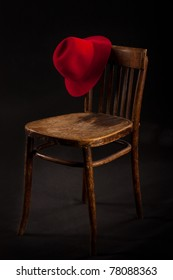 Red fedora hang on vintage chair, elements of gangster style or tango conceptual scene.