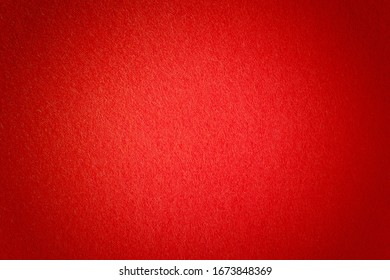 Red felt closeup background with vignette. Soft natural wool material, surface of a casino poker table, carpet for a ceremony.