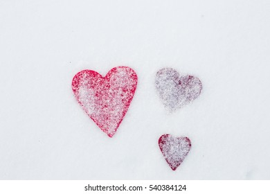 Red felt heart in snow, Valentine's Day. Copy space for text. Snowflakes on heart. Valentines day, love concept. White background