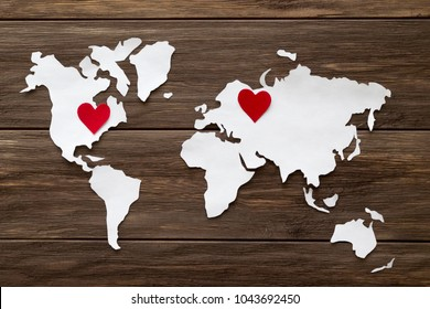 Red felt hearts and world map cutted from white paper on the wooden background. Long-distance relationships concept - Russia and United States. Flat lay, top view, copy space, mock up