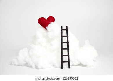 Red felted handmade heart over toy stuffing as a cloud and a wooden ladder to reach it./ It's not so hard to reach my heart