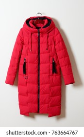 Red female winter jacket with a hood without fur, with a zipper. Outerwear. A long crimson jacket, isolated on a gray background.