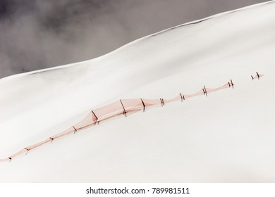 A red fence spanning across a deserted snowscape near Mt Schilthorn, Switzerland.