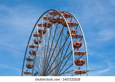Red Ferris wheel in front of blue sky