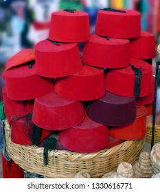 Red Fez tarbouche and white wicker tagine cookers, market medina of Marrakech,  Morocco