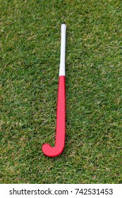 A red field hockey stick on green grass background.