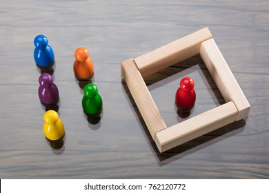 Red Figurine Pawn Separated By Wooden Blocks From Colorful Figurines