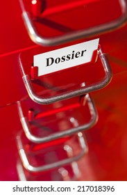 Red file cabinet with card Dossier - business background