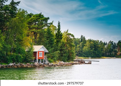 Red Finnish Wooden Sauna Log Cabin On Island In Summer