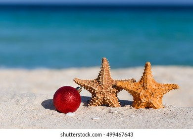 Red fir tree decoration ball and two starfishes on sandy beach, Tropical christmas and New Year celebration