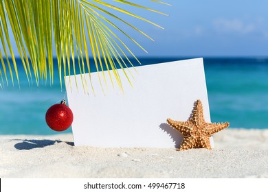 Red fir tree decoration ball and starfish near blank paper board on sandy beach, Tropical christmas celebration