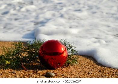 Red fir tree decoration ball on sandy beach