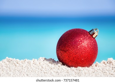 Red fir tree decoration ball on sandy beach, Tropical christmas and New Year celebration