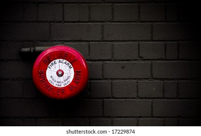 red fire alarm bell set against dark grey brick wall