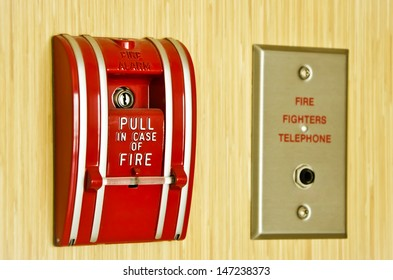 Red Fire alarm and fire fighter telephone on the wooden wall