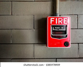 Red Fire Alarm on gray brick wall in building
