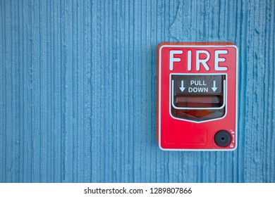 red fire alarm switch at blue cement wall inside the hotel building