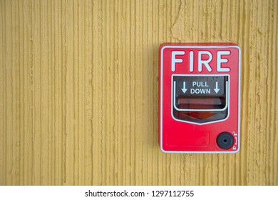 red fire alarm switch at yellow cement wall inside the hotel building