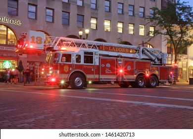 A red fire department ladder truck or Quint apparatus responding with lights flashing to an alarm with or call for assistance - Indianapolis, Indiana, USA - July 23, 2019
