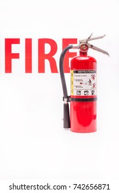 Red fire extinguisher with red fire letters in background