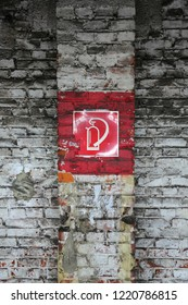 Red fire extinguisher sign on weathered brick wall