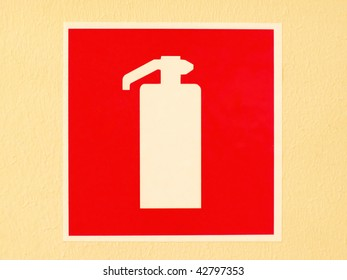 Red fire extinguisher sign/label on the orange wall