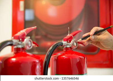 Red Fire extinguishers in the building,Engineers are checking fire extinguishers.