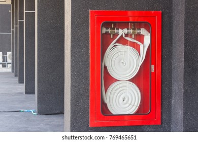 the red fire hose reel on the wall of the building