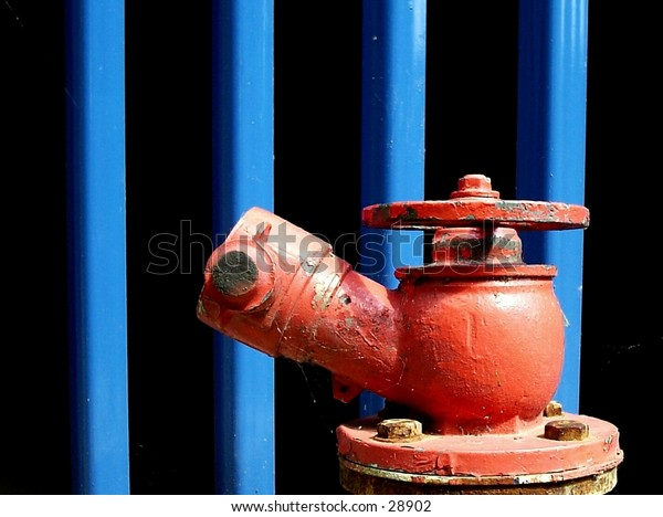 Red fire hydrant in front blue railings.