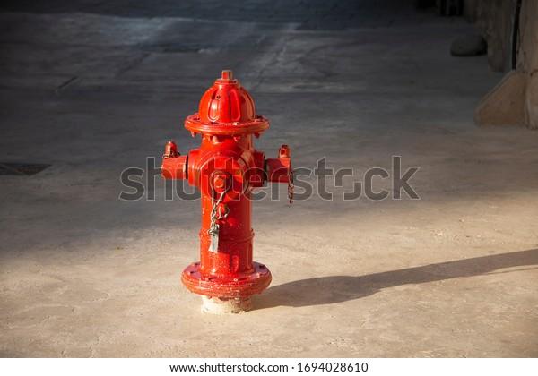 A red fire hydrant on a street sidewalk