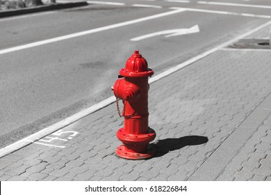 Red fire hydrant in otherwise black and white street scene.