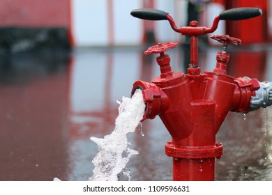 Red fire hydrant. It's pouring.